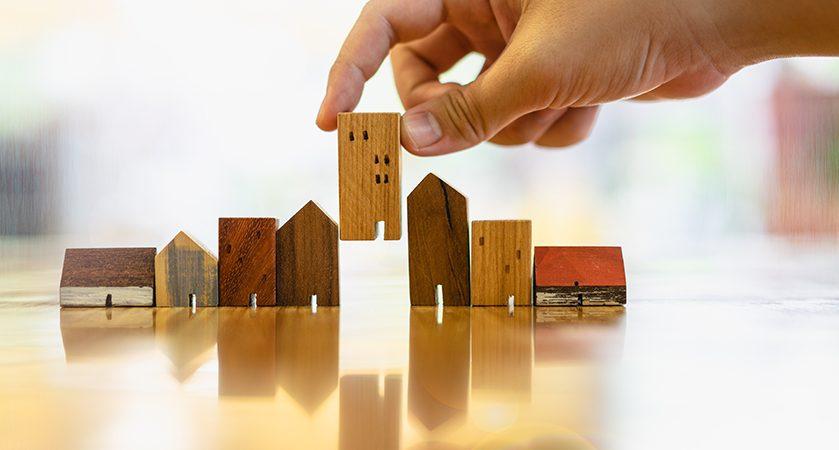 Hand choosing mini wooden house model
