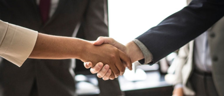 Close up of business partners shaking hands with buy sell insurance