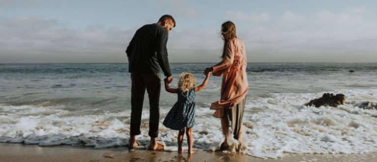 Parents with child at beach with toronto life insurance