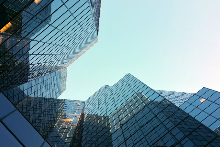 Looking up at towering commercial property buildings