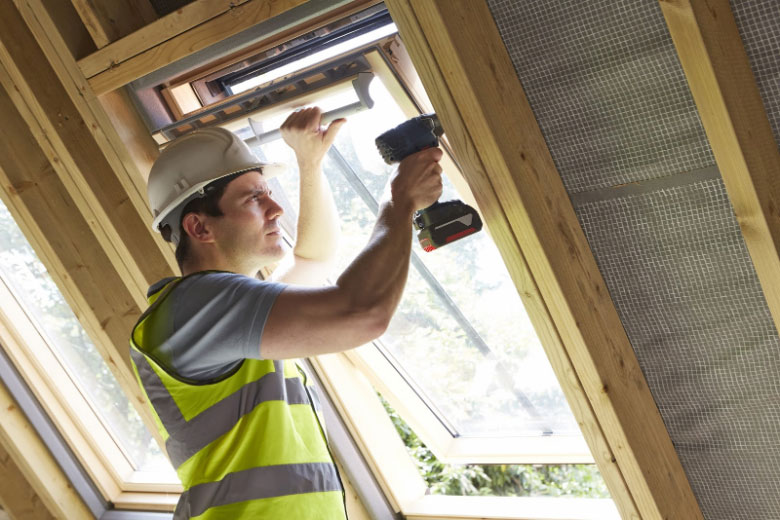 Contractor using a power drill while installing a window