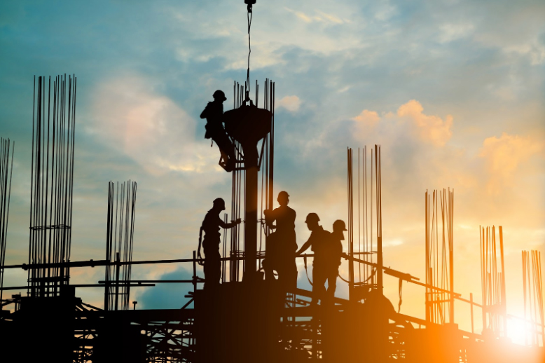 Silhouette of a construction team working on a high-rise building