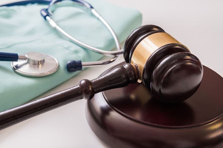 Close up of a judge's gavel beside a doctor's attire and stethoscope