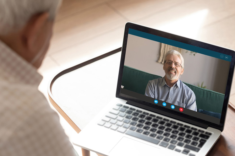 Elderly resident of long-term care facility utilizing video call to keep in touch with loved ones