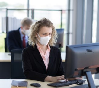 Employees wearing facemasks in an office setup