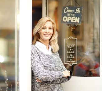 Business owner standing in front of her shop