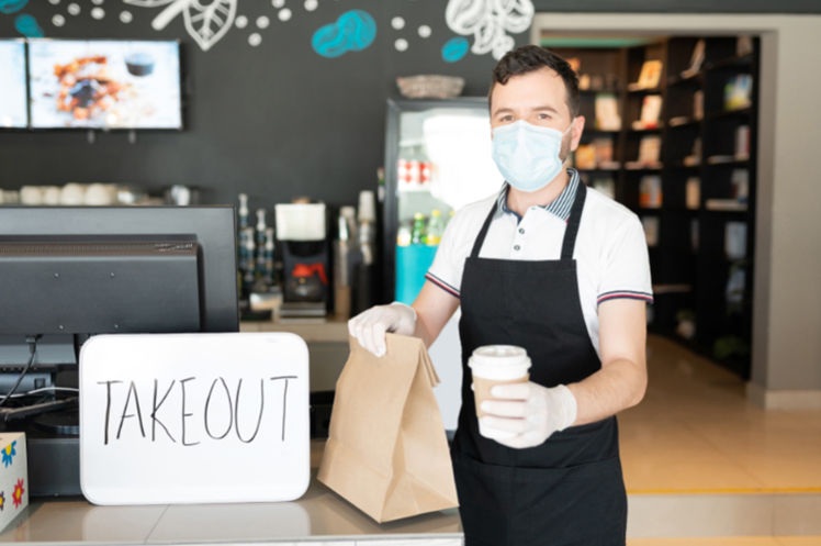 Restaurant staff standing beside a takeout sign, handing out an order