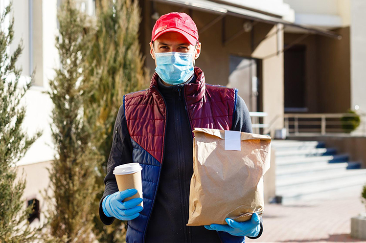 Food delivery man wearing gloves and a mask