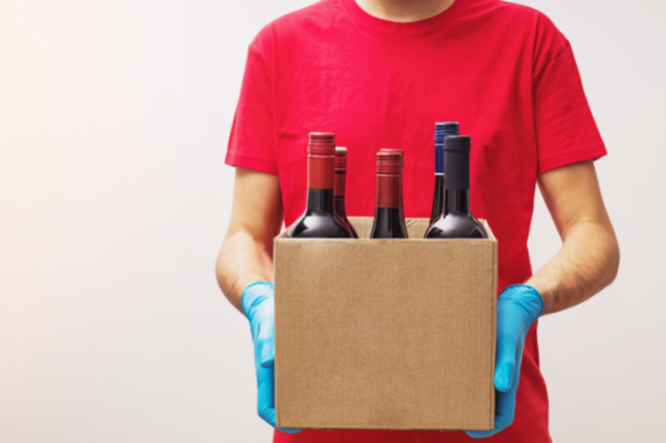 A delivery personnel wearing gloves and holding a box filled with wine bottles