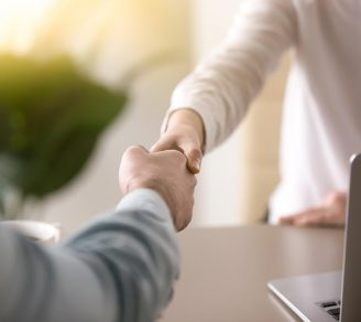 A commercial insurance broker and business owner shake hands