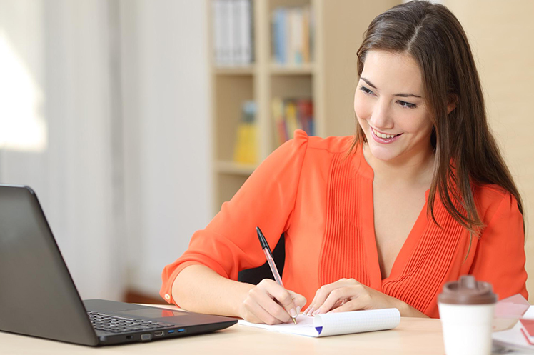 Enthusiastic businesswoman doing online research while taking down notes