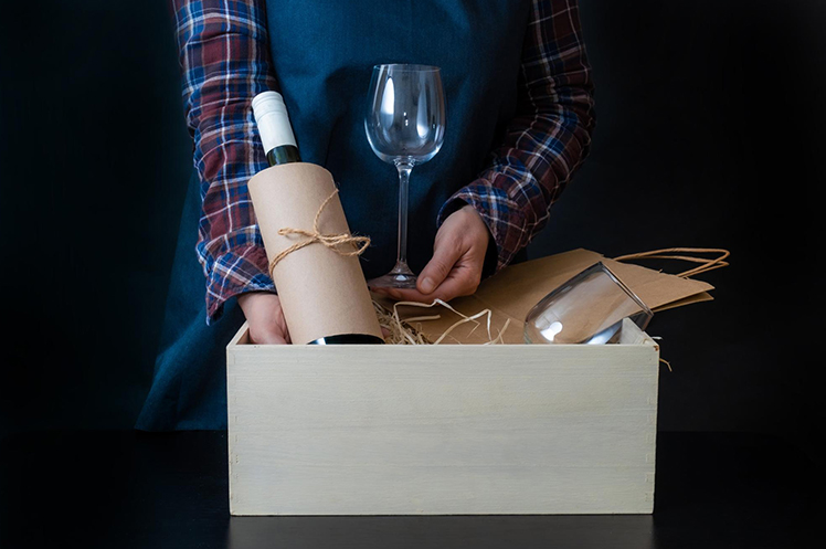 A wine delivery package being prepared, complete with wine glasses