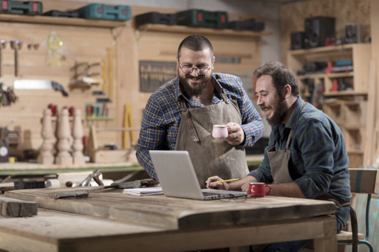 Two small business owners in their workshop, researching on a laptop
