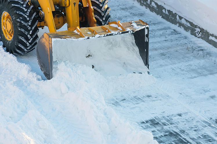 Close-up of a tractor clearing snow away