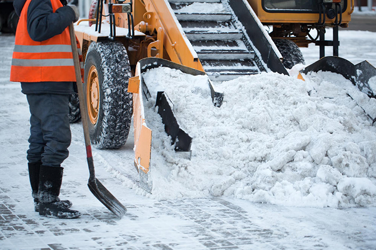 A tractor clears snow beside a snow removal contractor