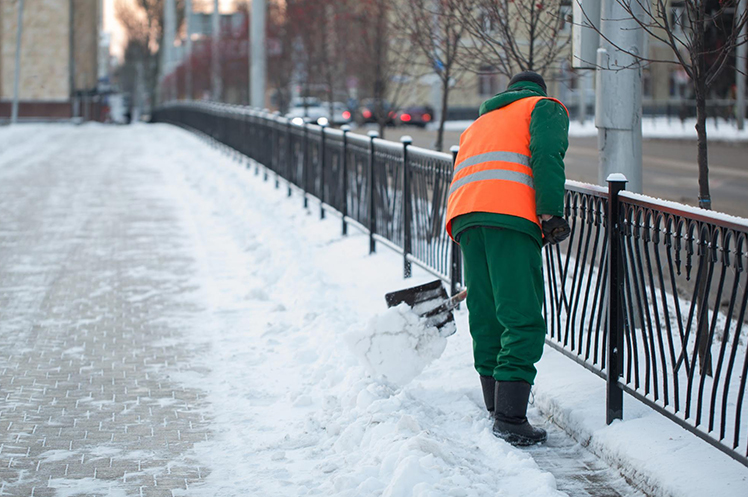 A snow removal contractor shovels the snow from the streets