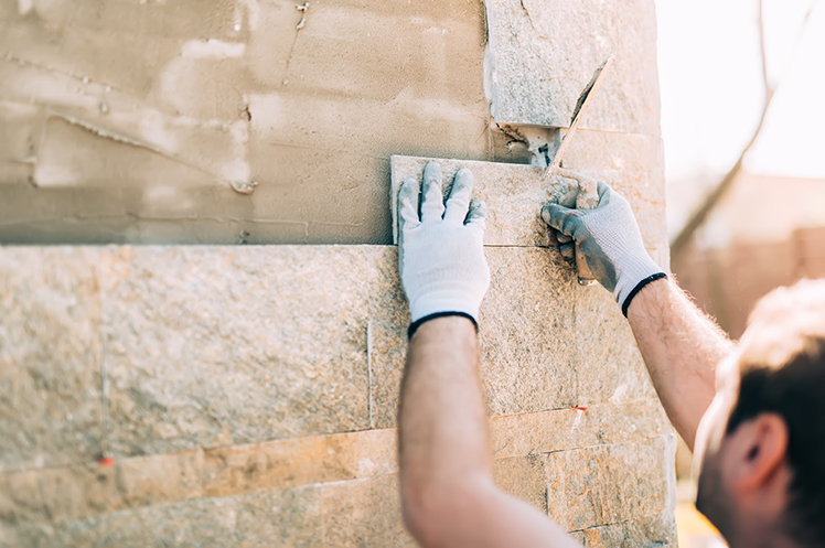 Stone mason contractor working on a wall