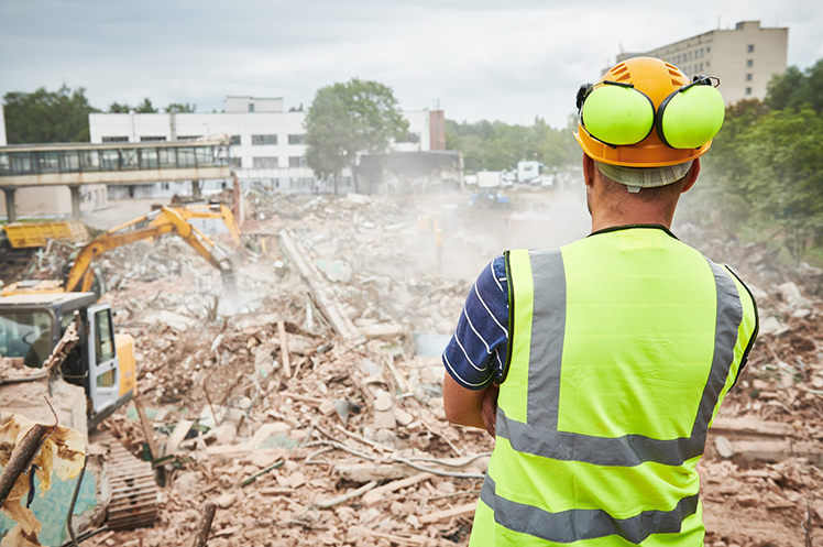 Demolition contractor looking at accomplished demolition work