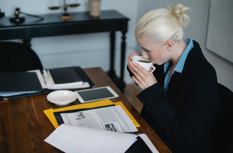An attorney sitting at her desk, reviewing case documents while sipping coffee