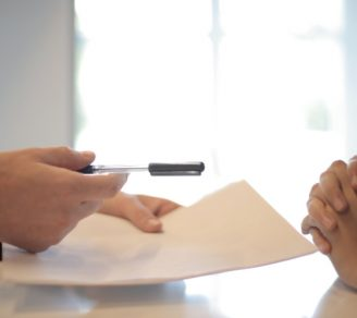 An insurance broker handing a document to a business owner to sign