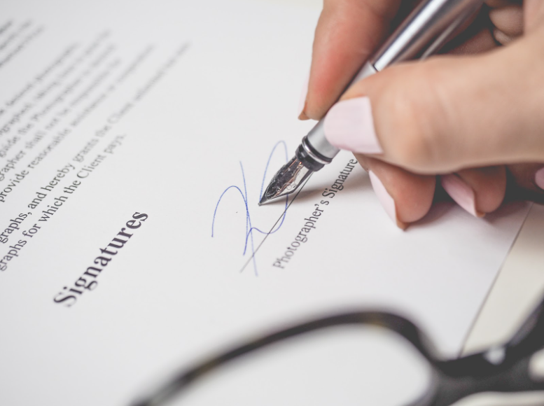Close-up of a hand of someone signing a contract