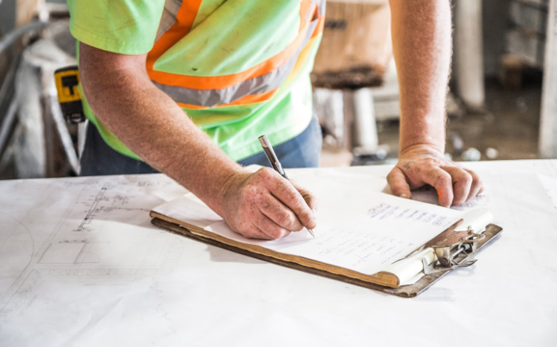 A construction supervisor signing a document on a clipboard