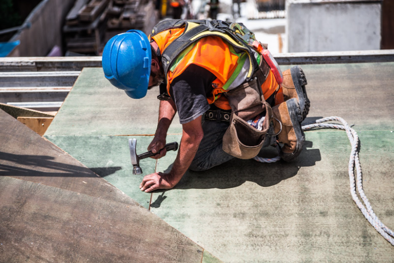 A construction employee hammering down a nail