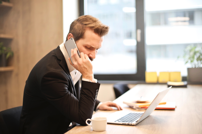 Perplexed businessman looking at his laptop while talking on the phone