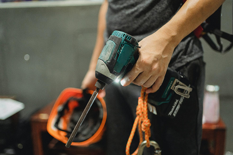 Close-up of a renovation contractor holding a power drill and orange hard hat