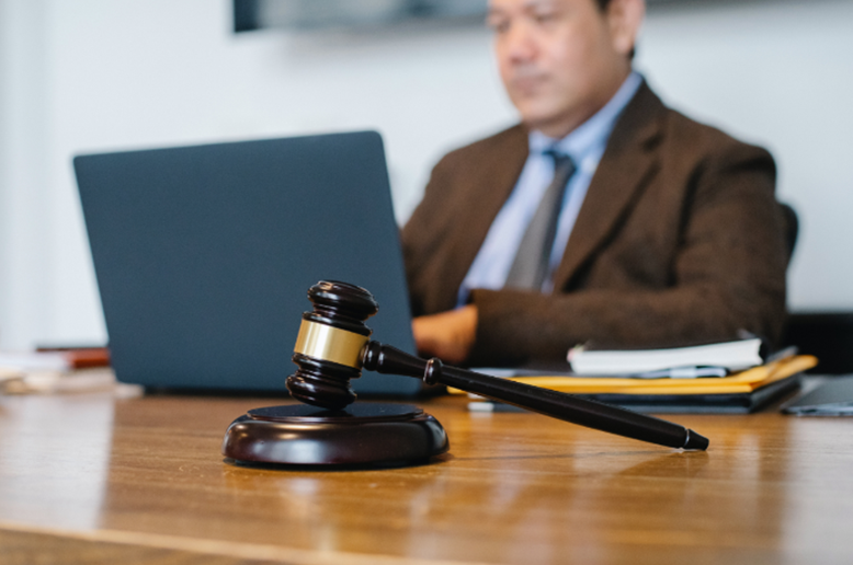 An attorney intently at work on his laptop with a mallet and gavel at the foreground