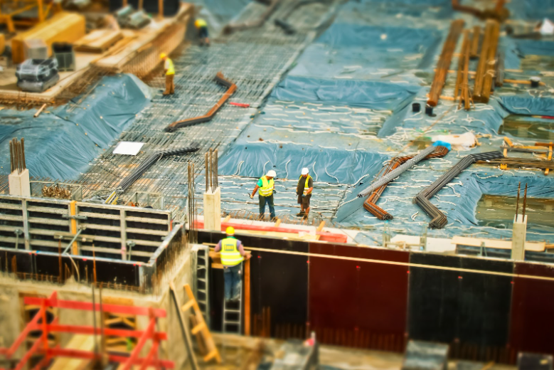 Overhead shot of an ongoing construction project and three construction workers