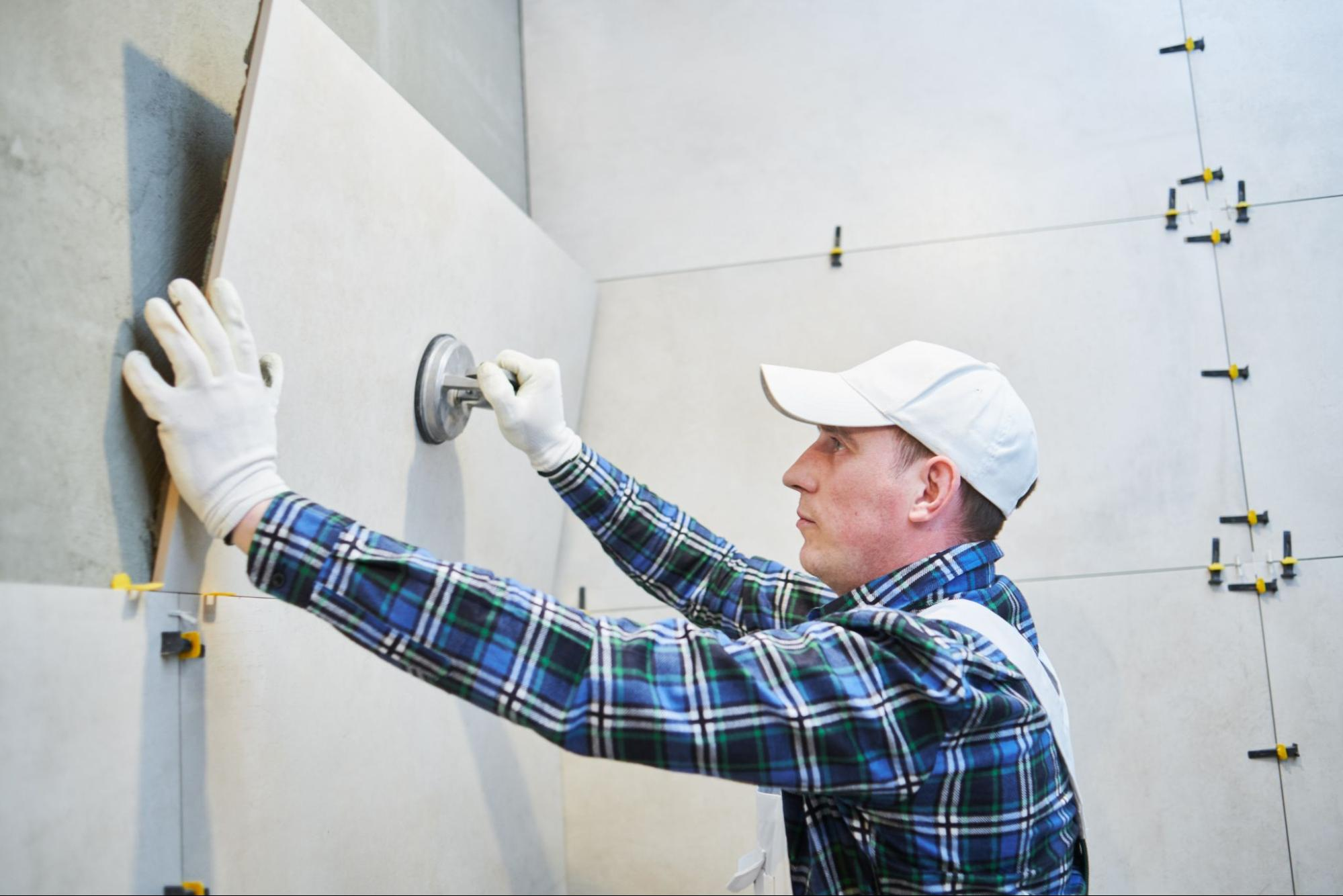 A focused home renovation contractor installing a large tile