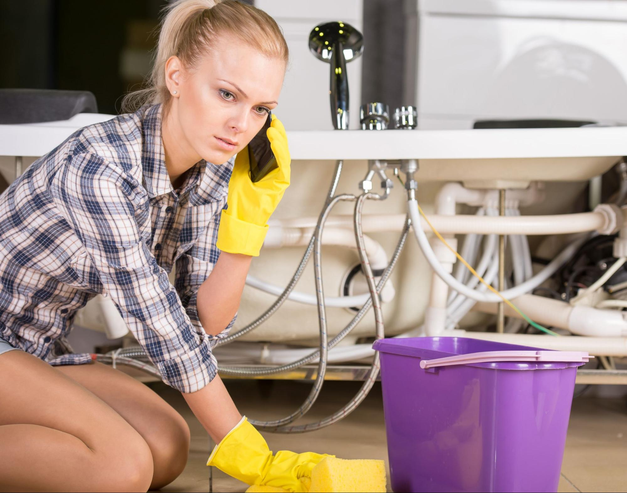 Upset woman cleaning up puddles from a pipe leak while talking on the phone