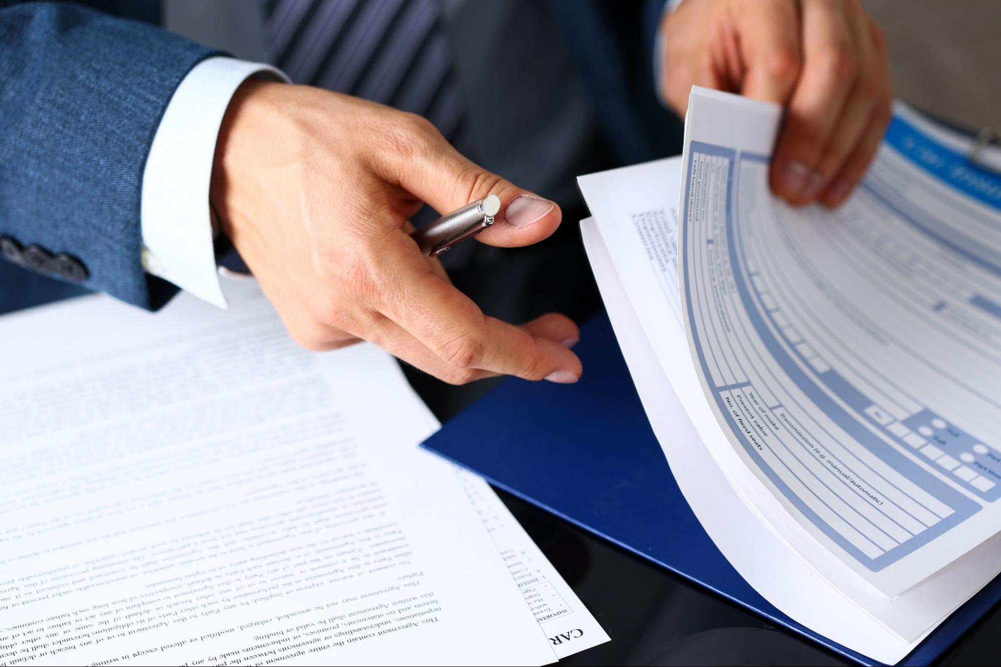 A closeup of a commercial property insurer's hands as he flips through insurance papers