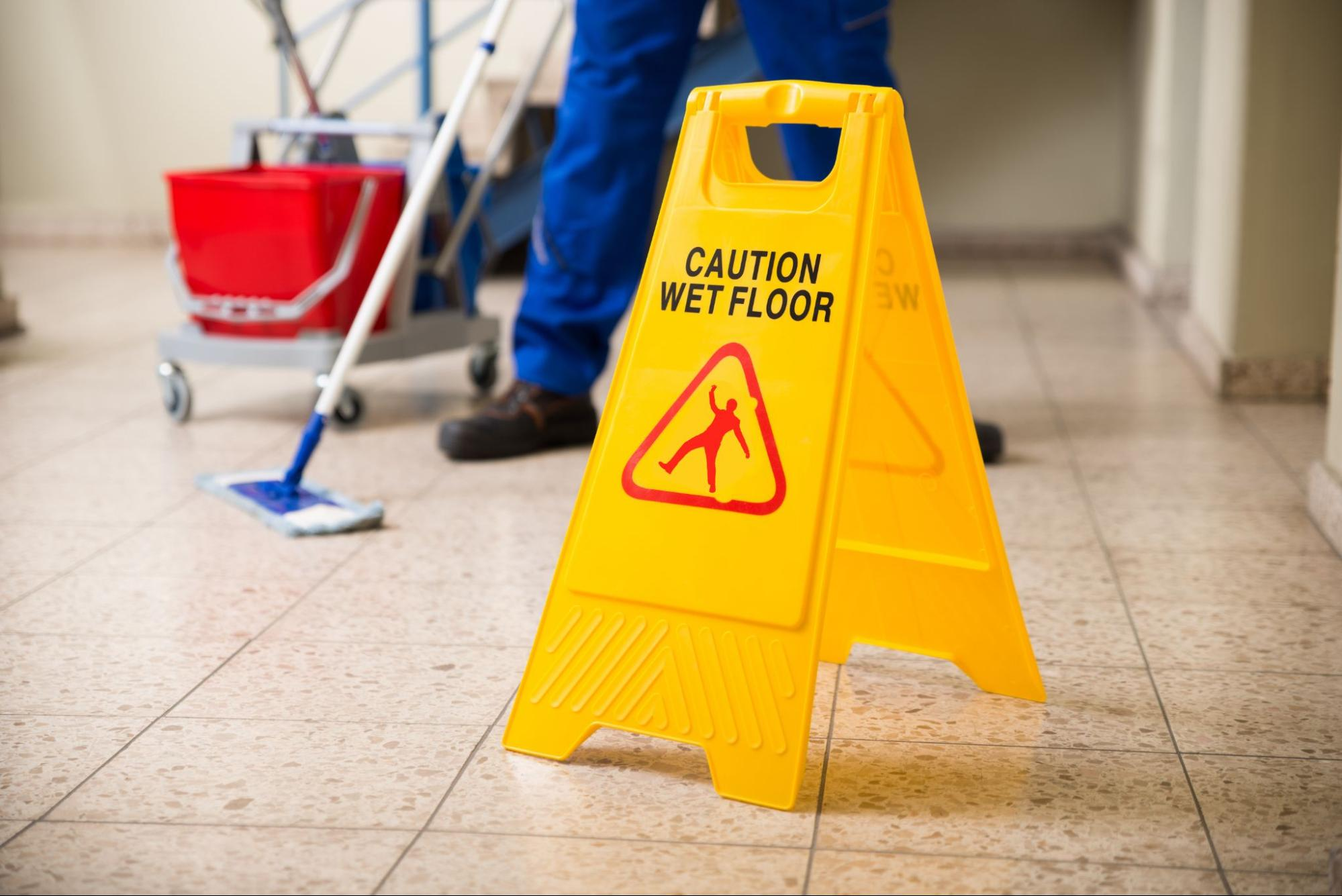 """Close up of a """"Caution Wet Floor"""" signage on a floor that's being mopped"""