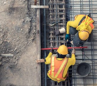 An overhead shot of two construction workers at work in a construction site