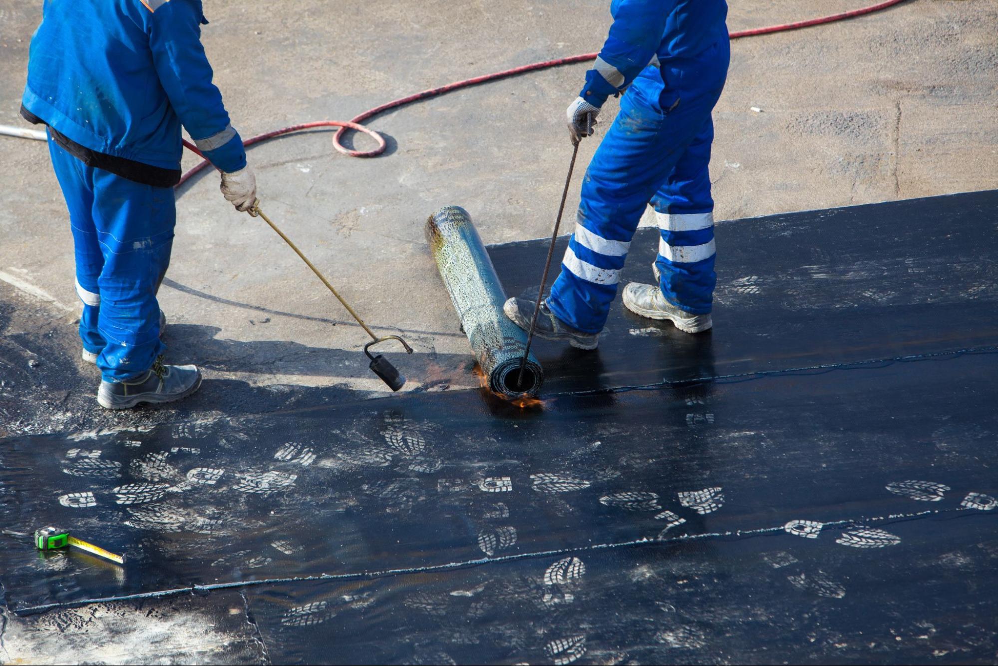 Waterproofing contractors applying a waterproof coat
