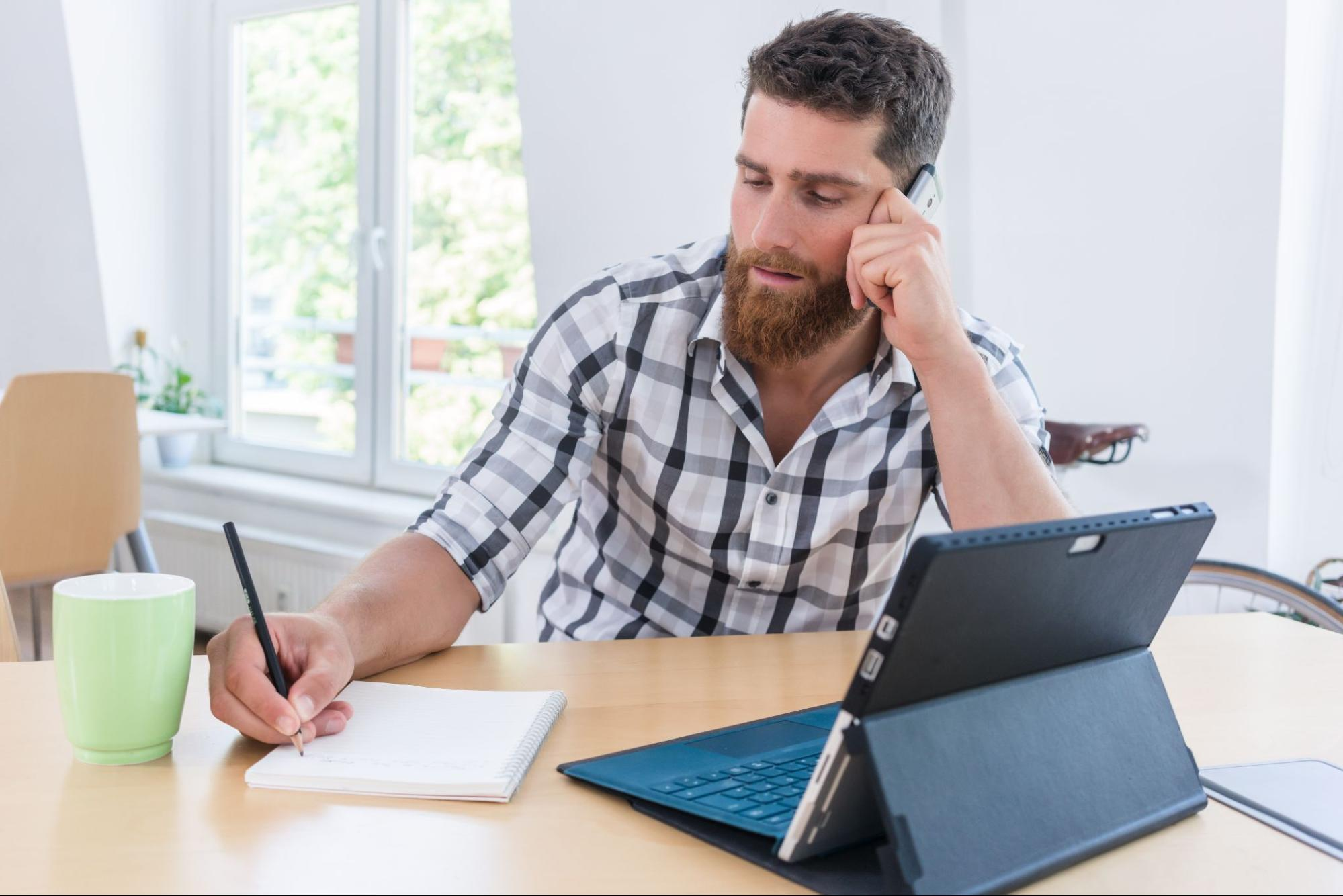 An independent contractor taking notes at home while on a phone call