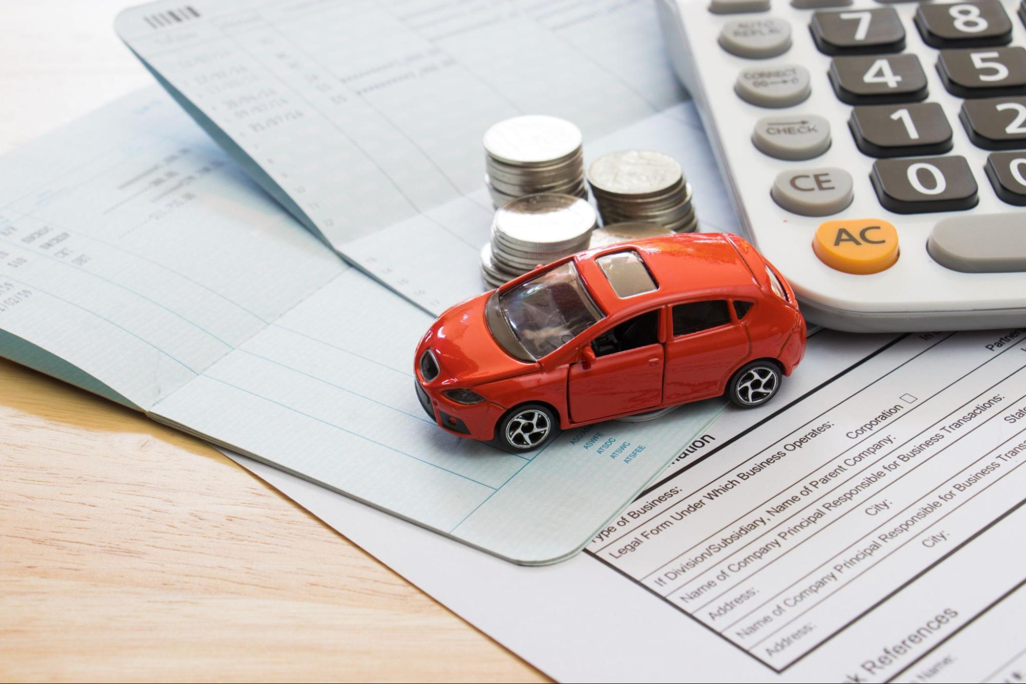 A miniature car on paper documents, coins, and a calculator, representing car insurance