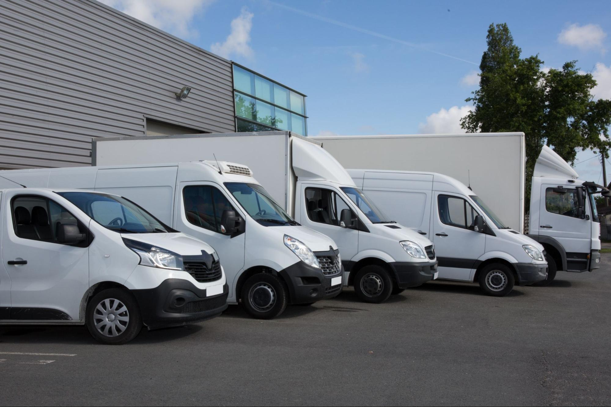 Various commercial vehicles parked in front of a company