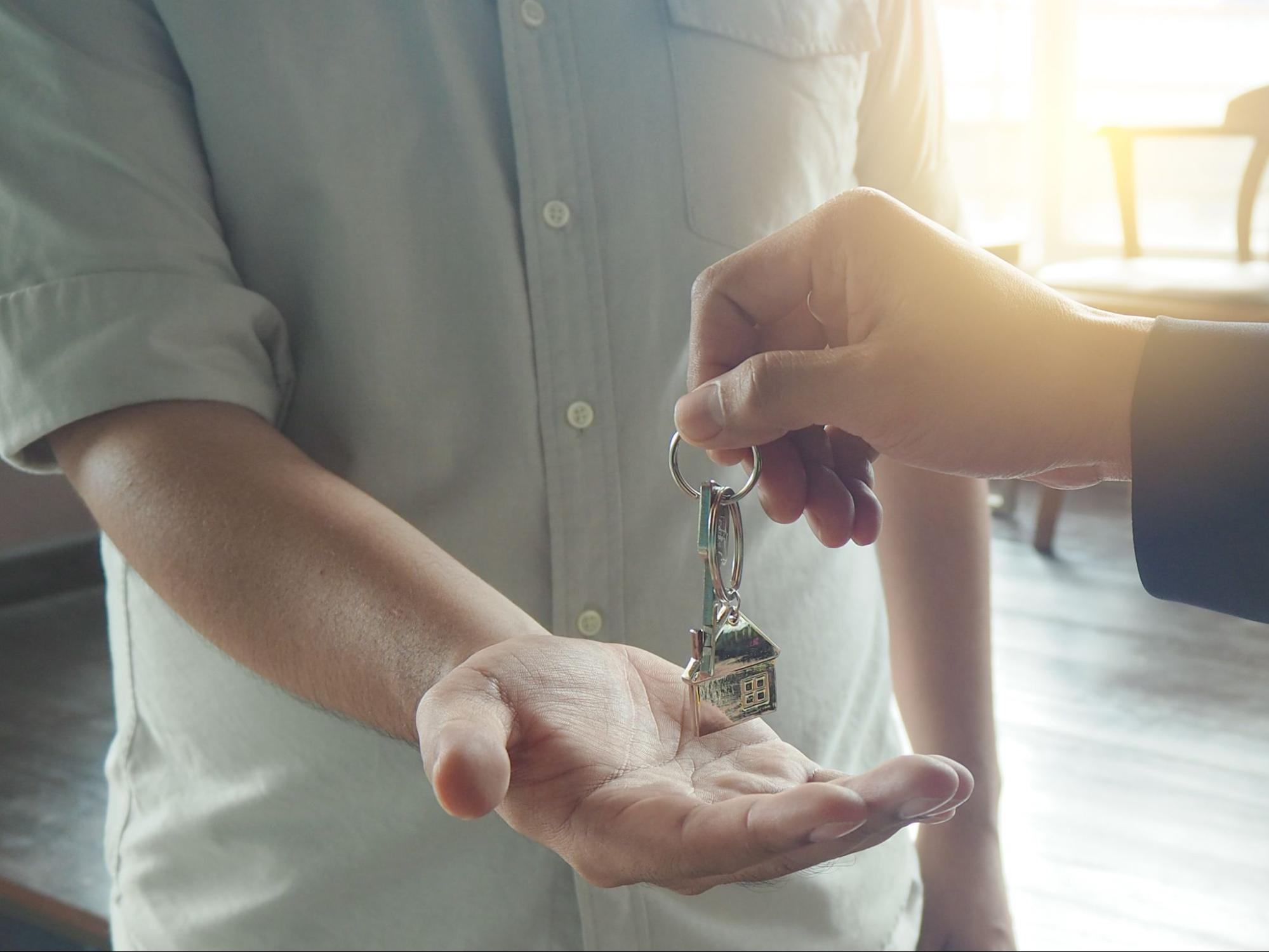 A cropped image of a landlord's hands giving keys to the tenant