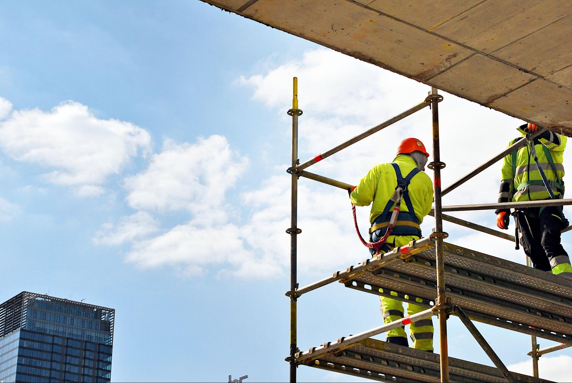 Two construction workers on scaffolding, covered by scaffolding insurance