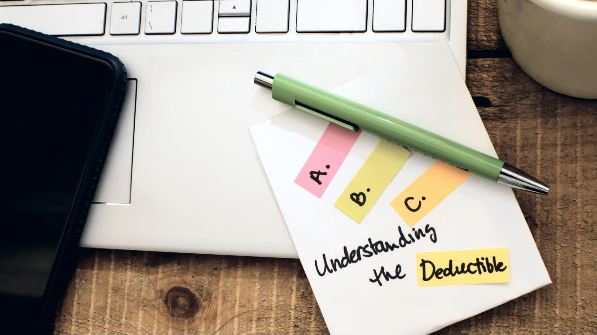 """Close-up of a note on a laptop saying """"Understanding the Deductible"""""""