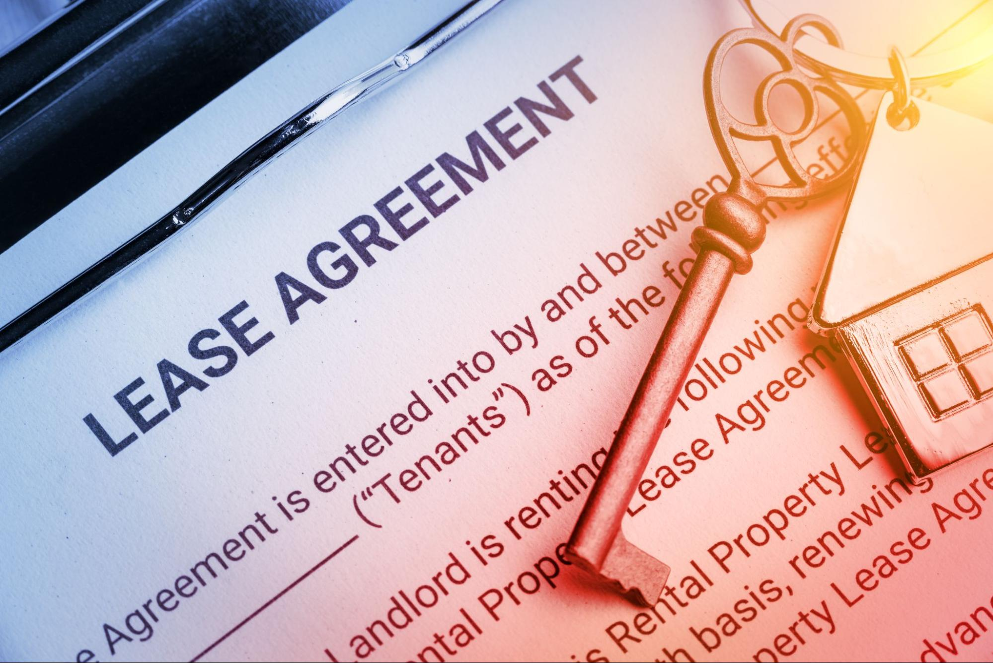 Close-up of lease agreement papers and a key to a rental property