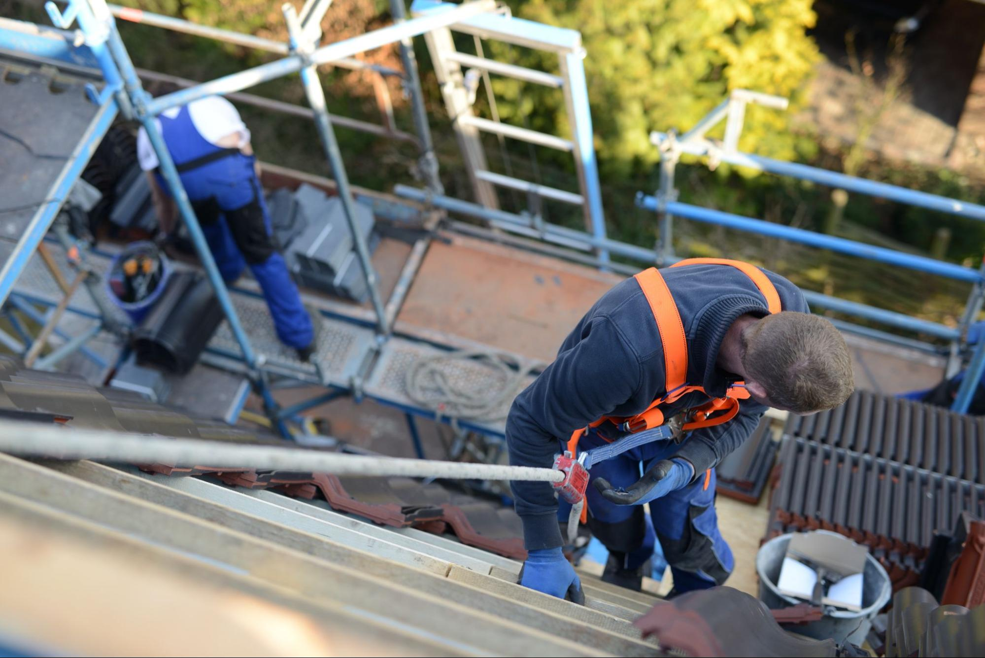 A roofing contractor on the roof with a safety harness