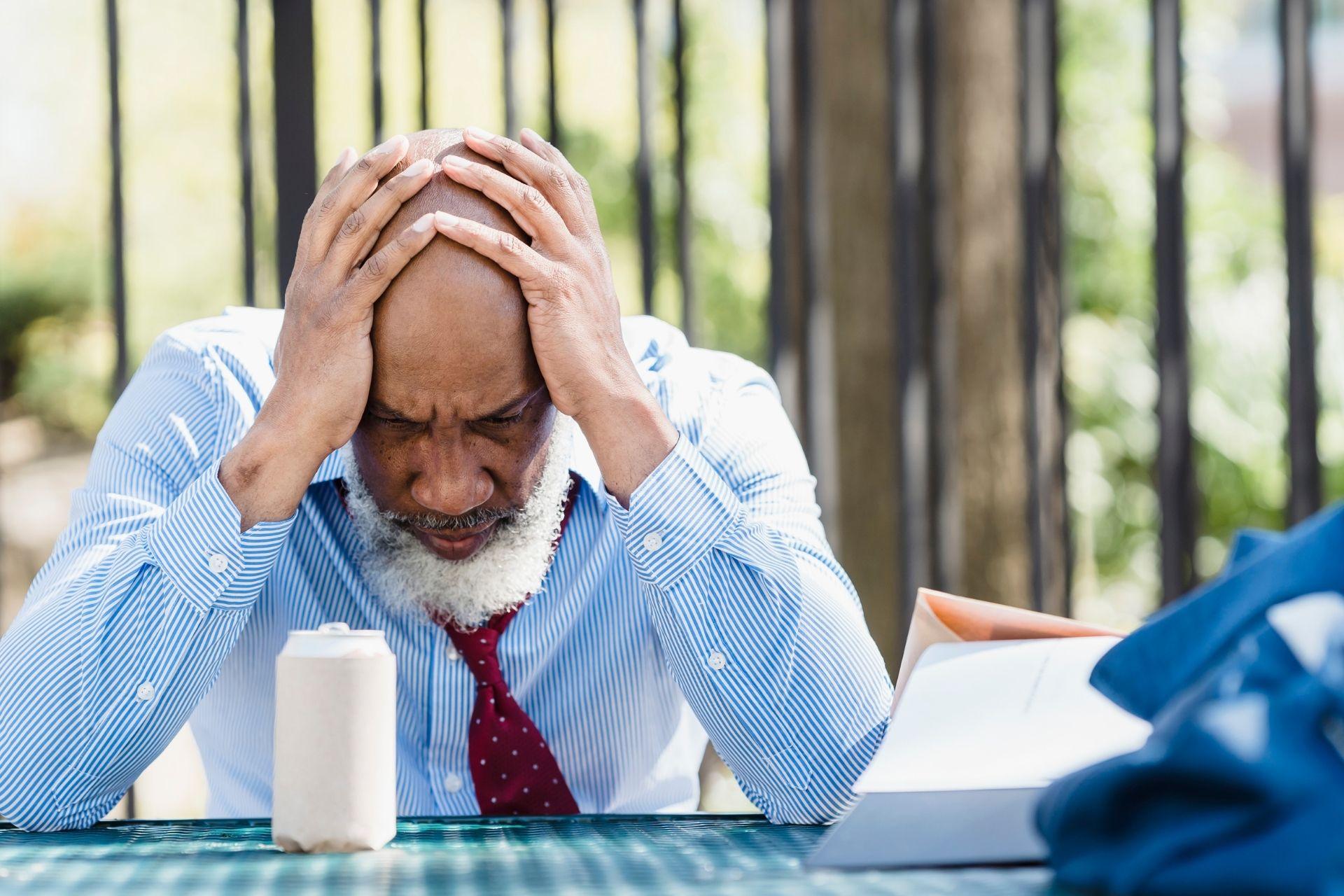 A man cradling his head, feeling worried
